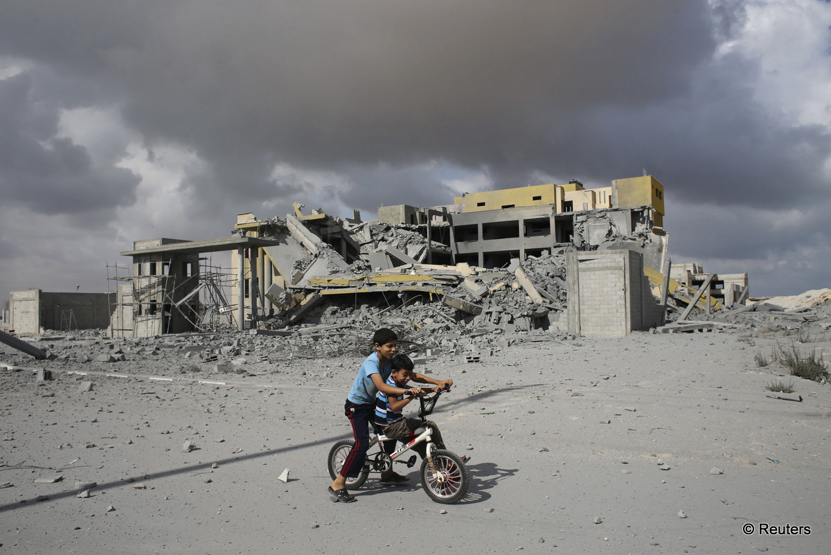 Palestinian boys ride a bicycle past a police station, which was under construction when it was destroyed in what police said was an Israeli air strike in Rafah in the southern Gaza Strip